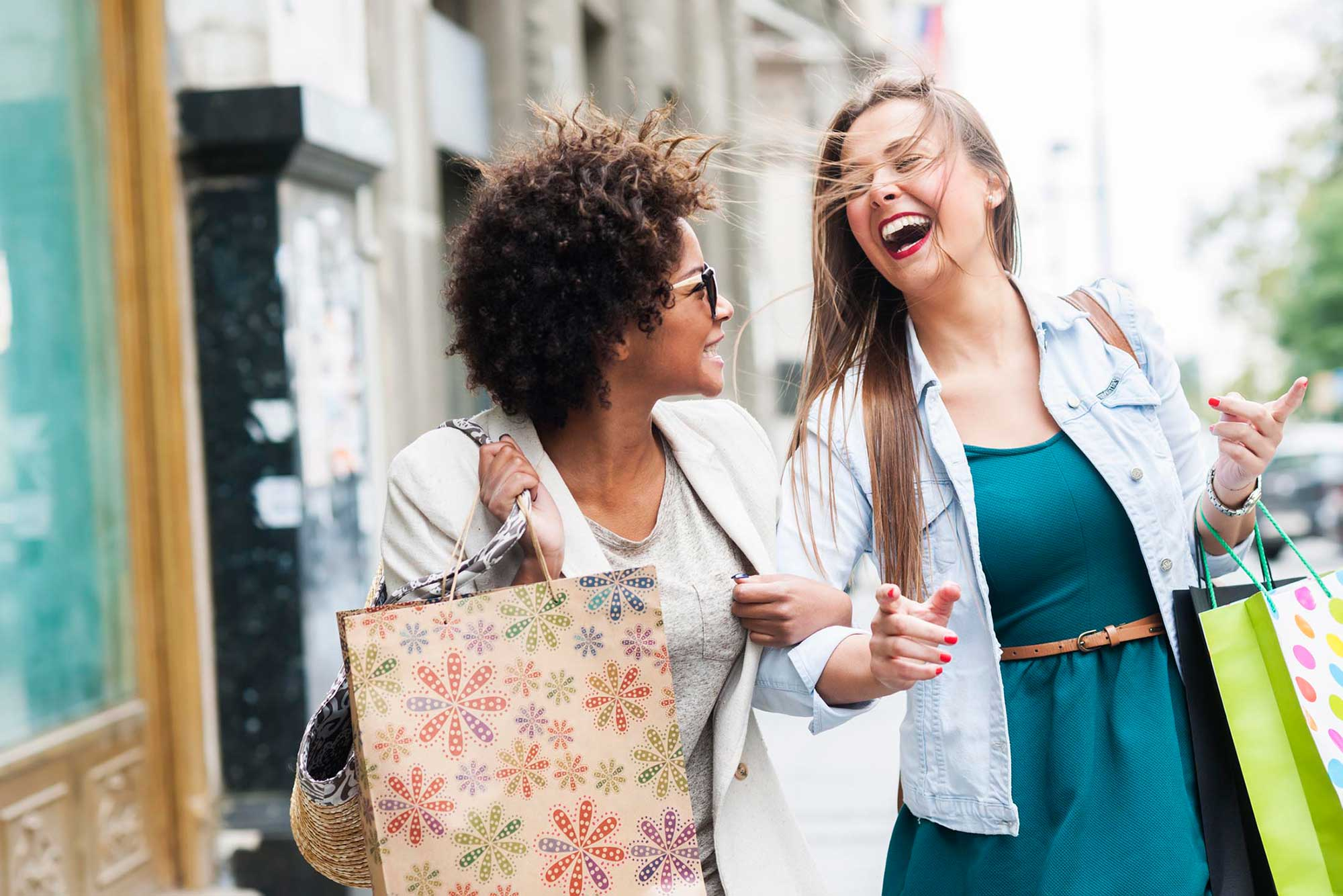 2 women shopping walking down the street laughing